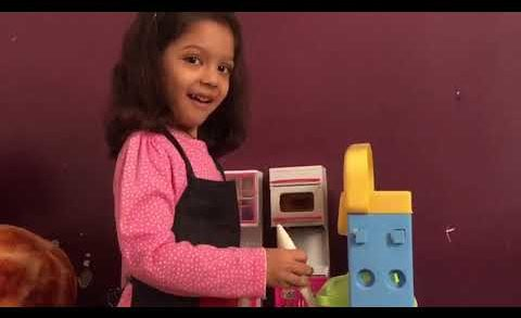 Little Girl Playing With Kitchen Set
